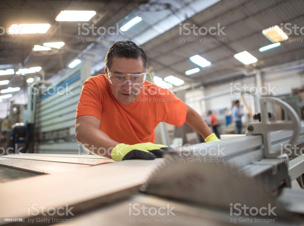 Man working at a lumberyard cutting wood stock photo