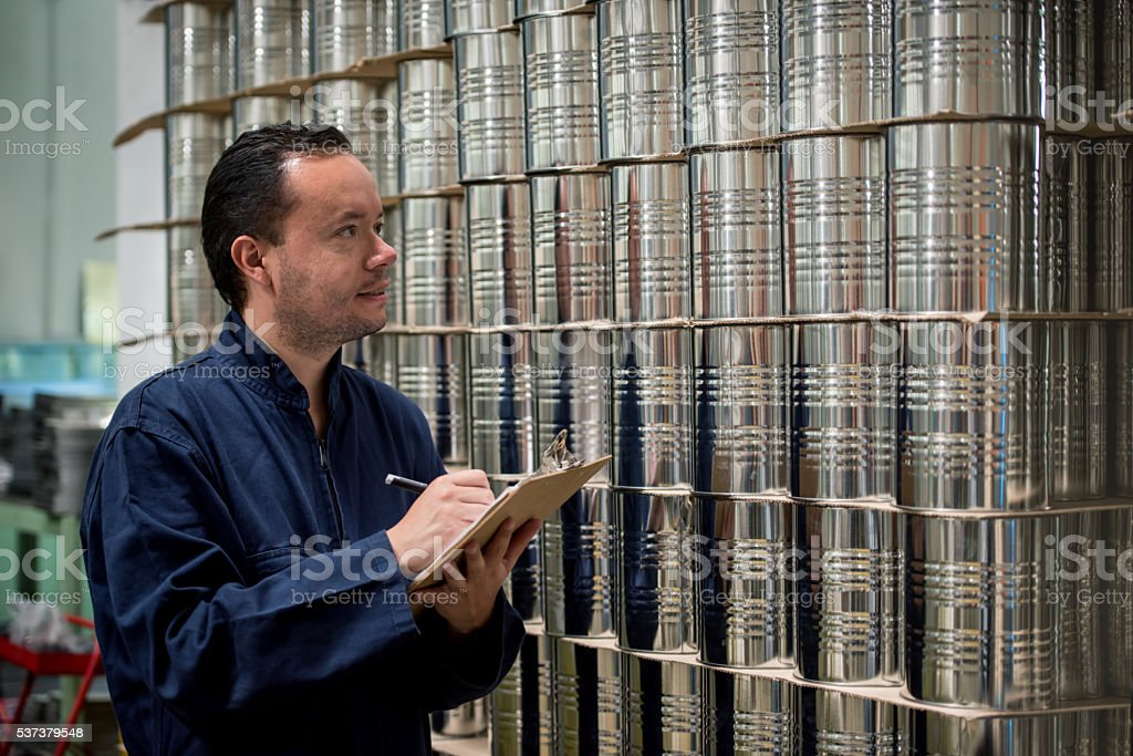 Man working at a metal factory and doing inventory stock photo