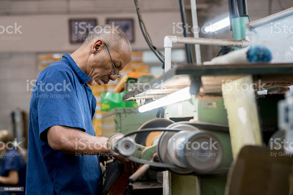 Man working at a shoe-making factory stock photo