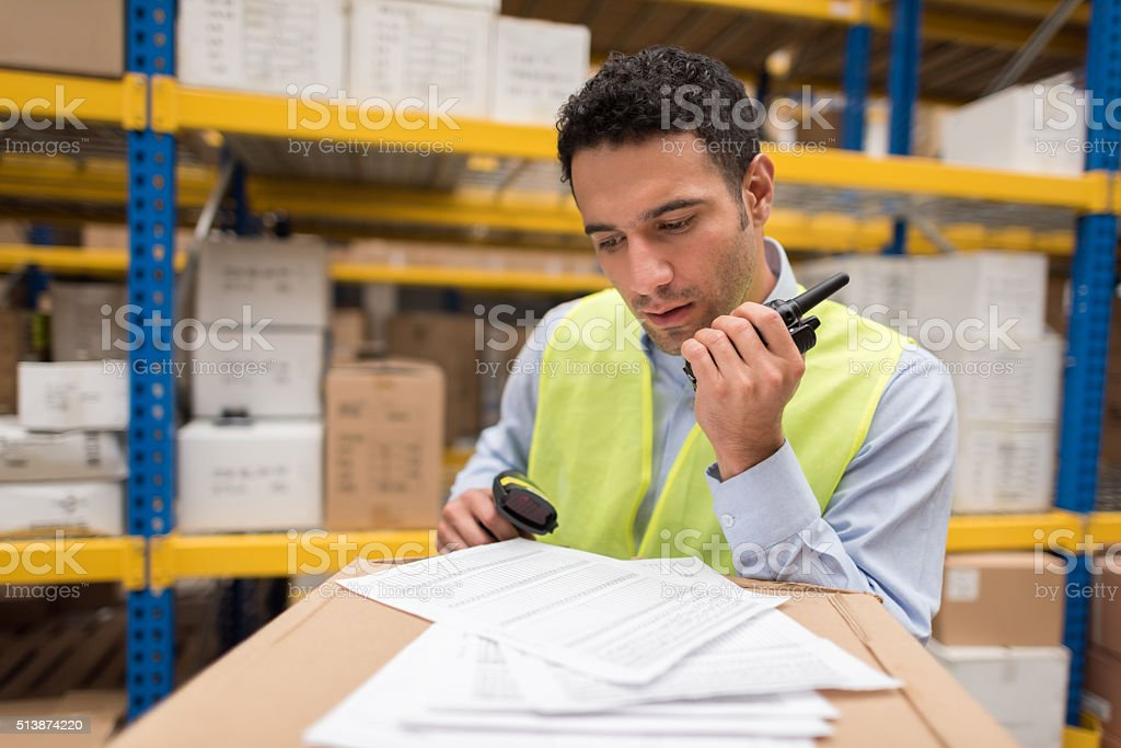 Man working at a warehouse doing inventory stock photo