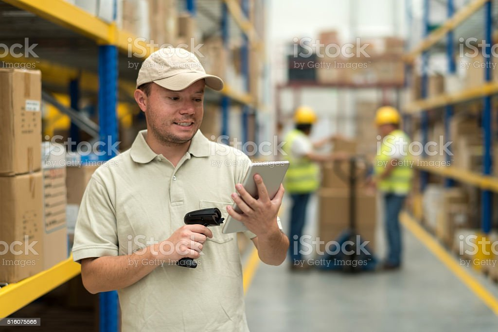 Man working at a warehouse doing the inventory stock photo