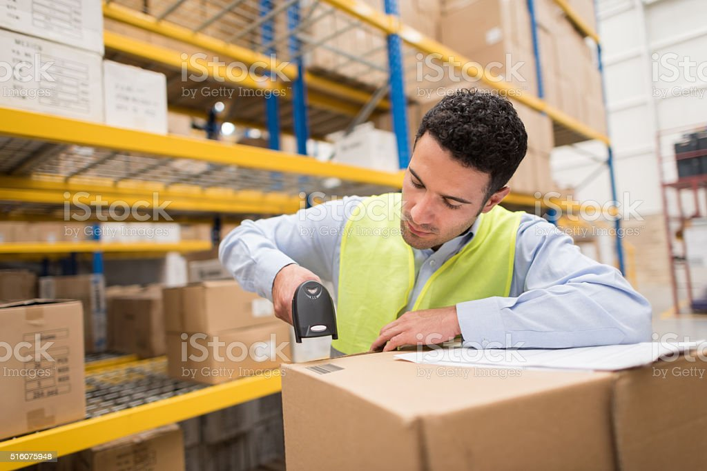 Man working at a warehouse scanning products stock photo