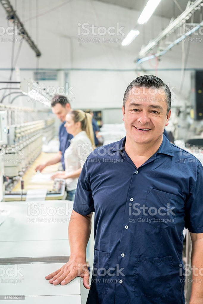 Man working at an embroidery factory stock photo