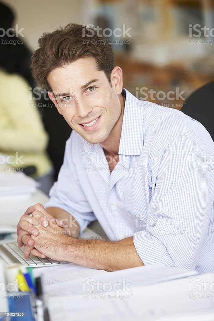 Man Working At Desk In Busy Creative Office royalty-free stock photo