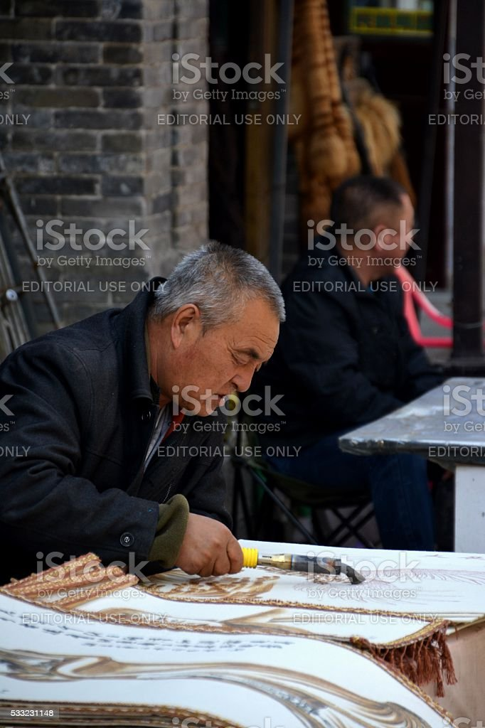 Man working at Paintings souvenir shop in Hohhot, Inner Mongolia stock photo