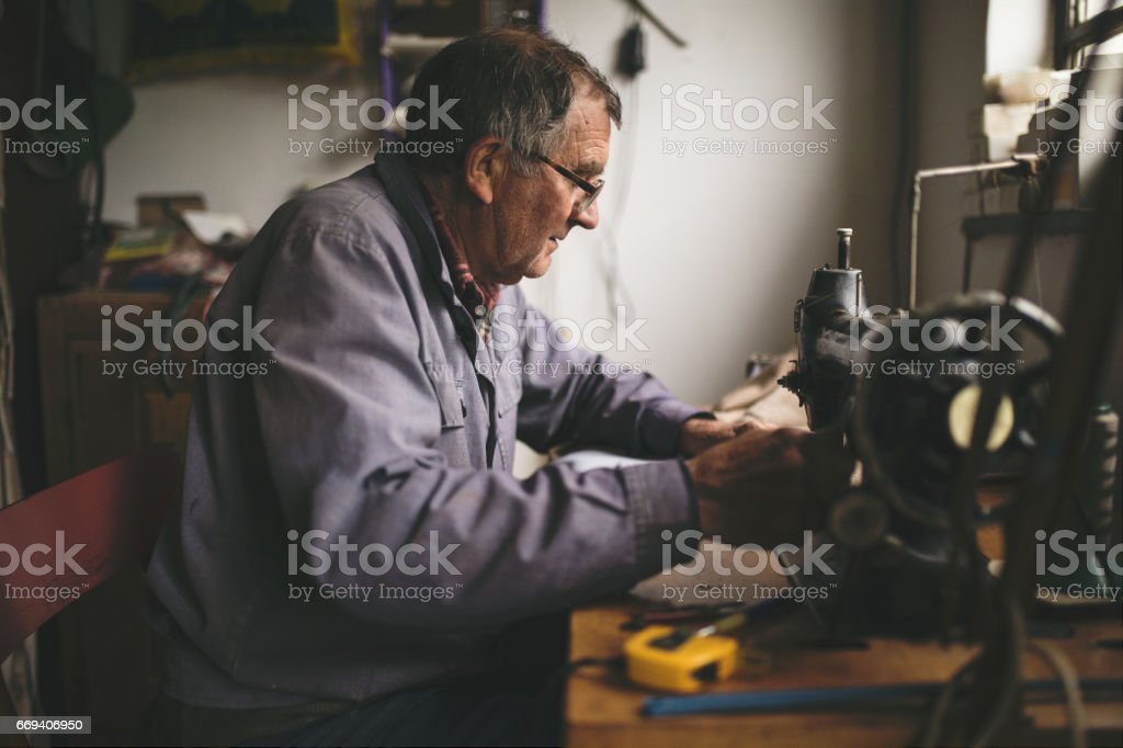 Man working at sewing machine stock photo