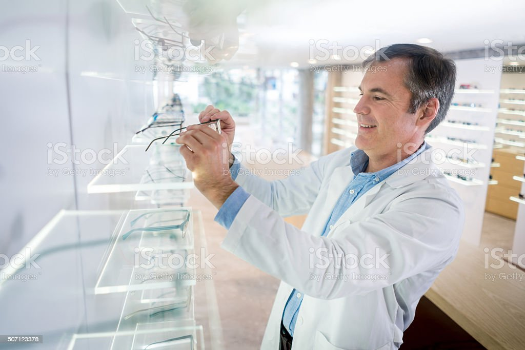 Man working at the optician's shop stock photo