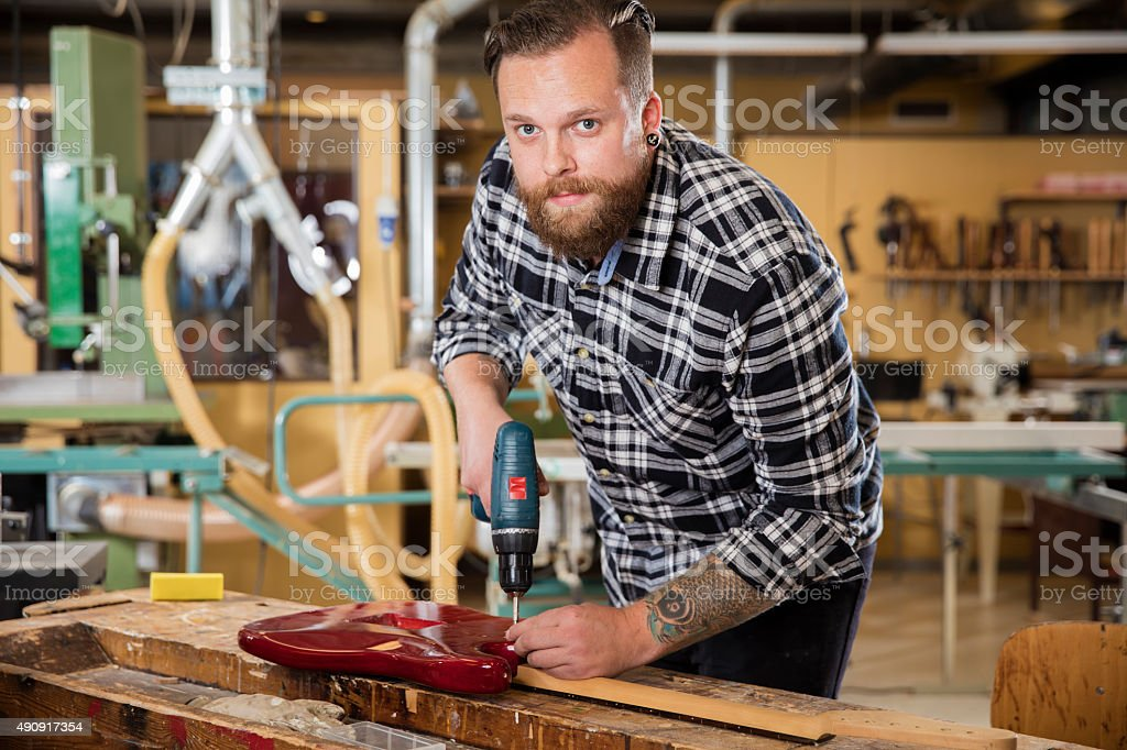 Man working at workshop with guitar stock photo
