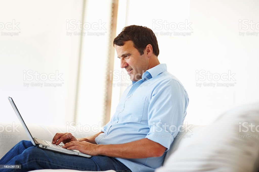 A man working from home on his laptop stock photo