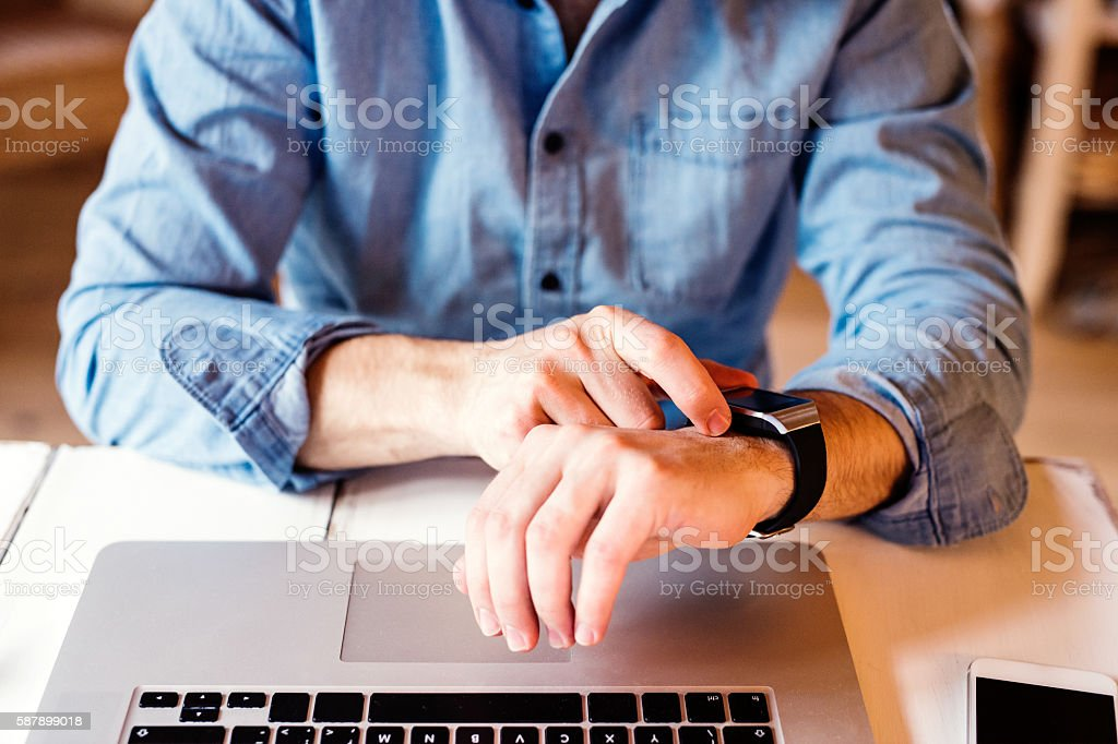 Man working from home on laptop, wearing smartwatch stock photo