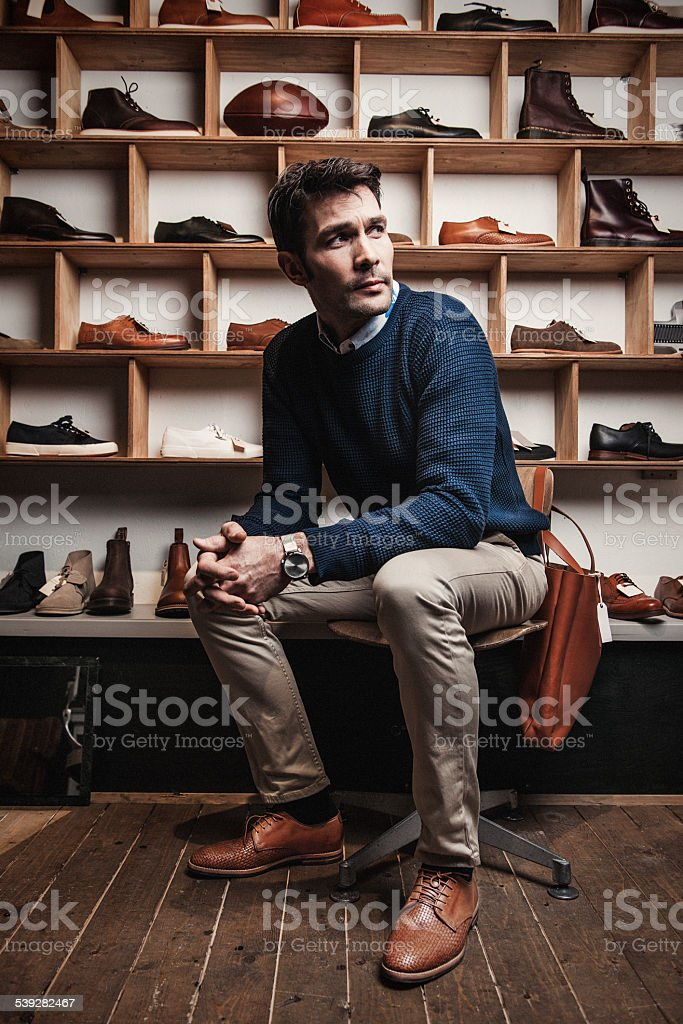 Man working in a small business retailer at shoe store stock photo