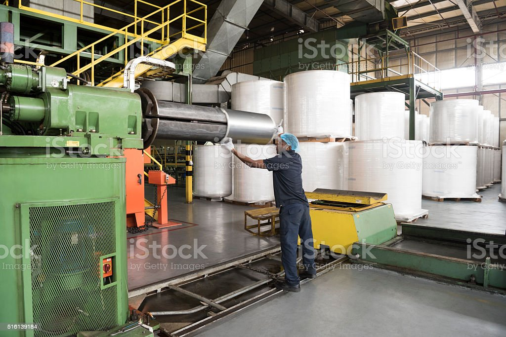 Man working in aluminium factory with machinery stock photo