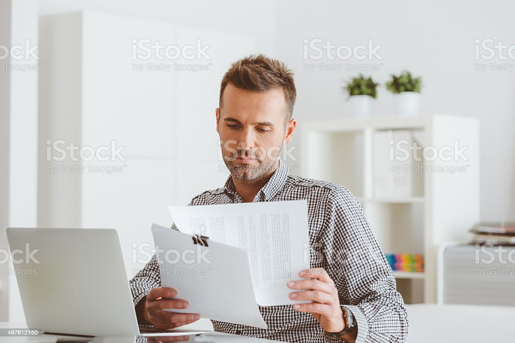 Man working in an home office, reading documents stock photo
