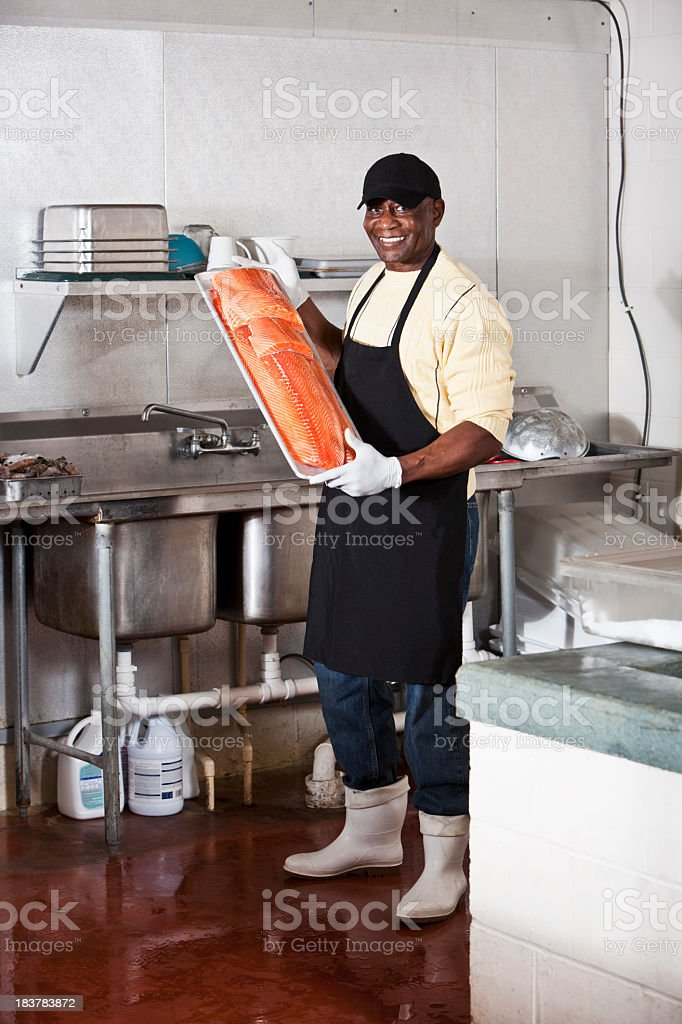 Man working in back room of fish market stock photo