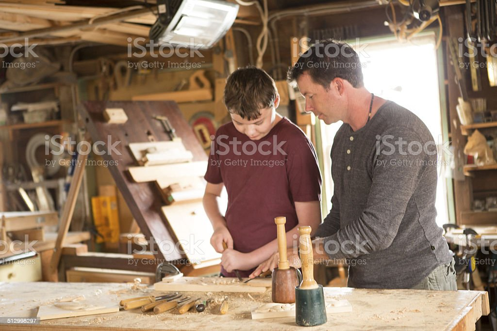 Man working in his workshop helping kid use chisel stock photo