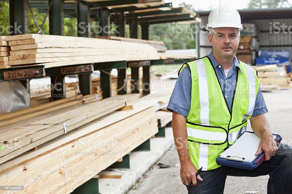 Man working in lumber yard stock photo