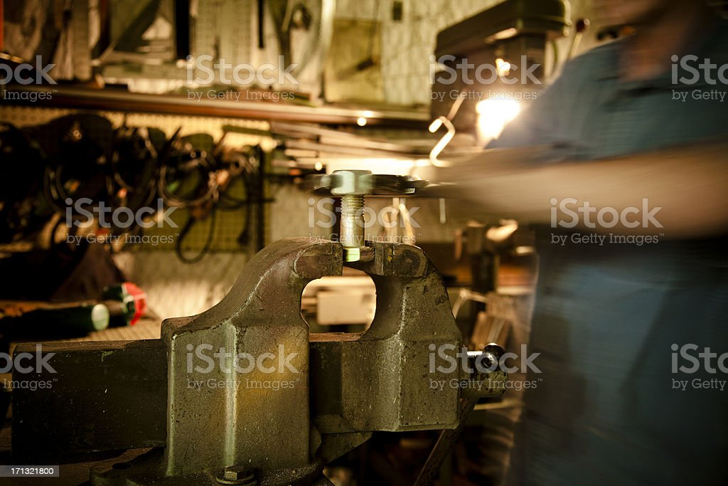 Man working in machine shop at vise stock photo