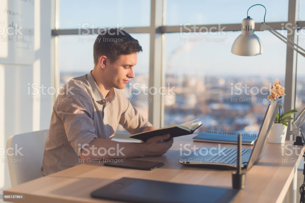 Man working in modern office, writing down new ideas his notebook, searching information using portable computer at workplace stock photo