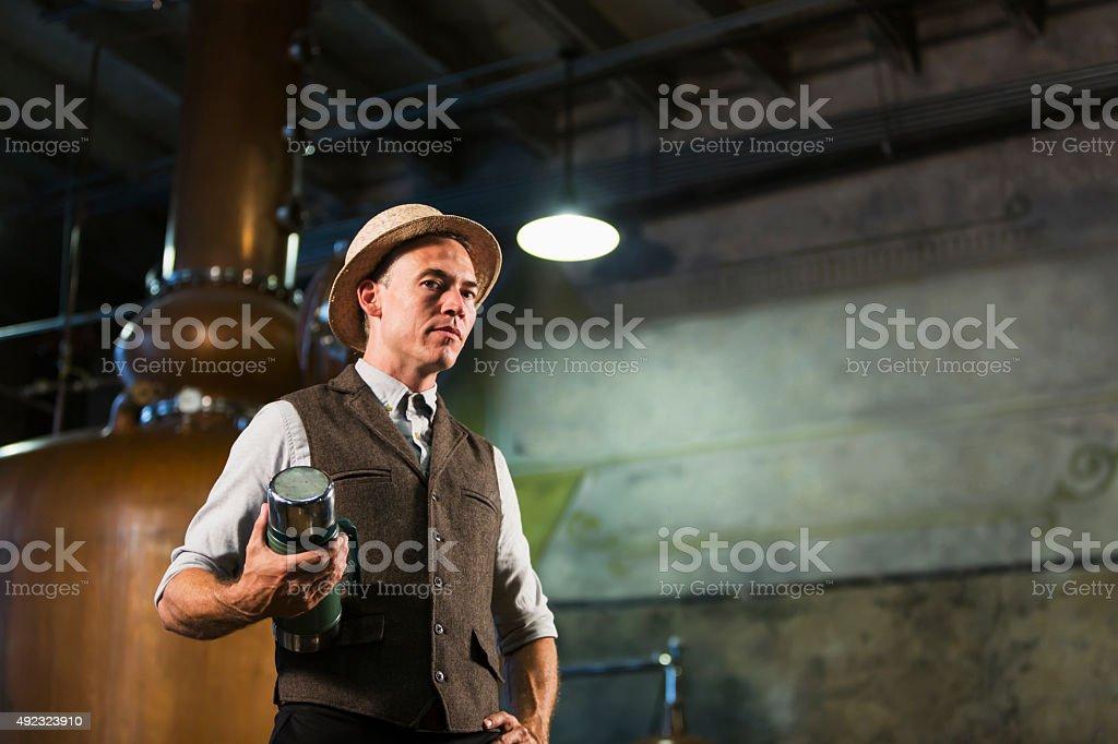 Man working in old distillery taking coffee break stock photo