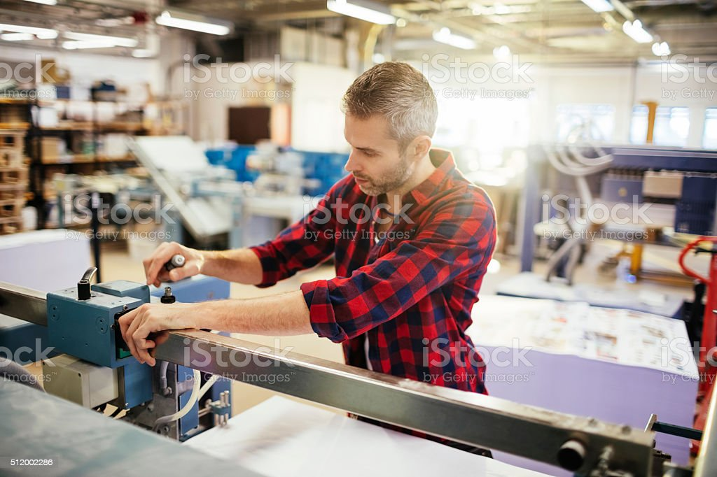 Man working in printing factory stock photo