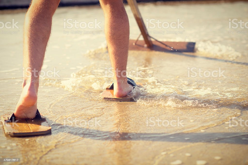 Man Working in Salt-Pan With Traditional Wood Tool and Sandals stock photo