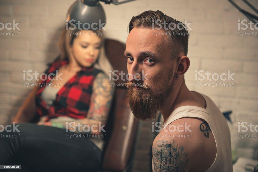 Man working in tattoo salon stock photo