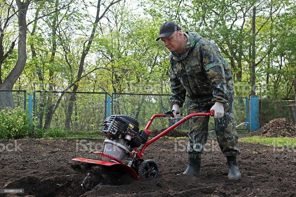 Man working in the garden preparing ground cultivator stock photo