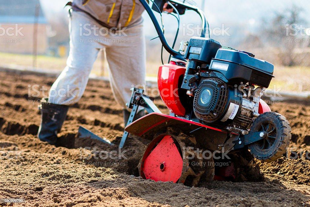Man working in the garden with Garden Tiller. stock photo