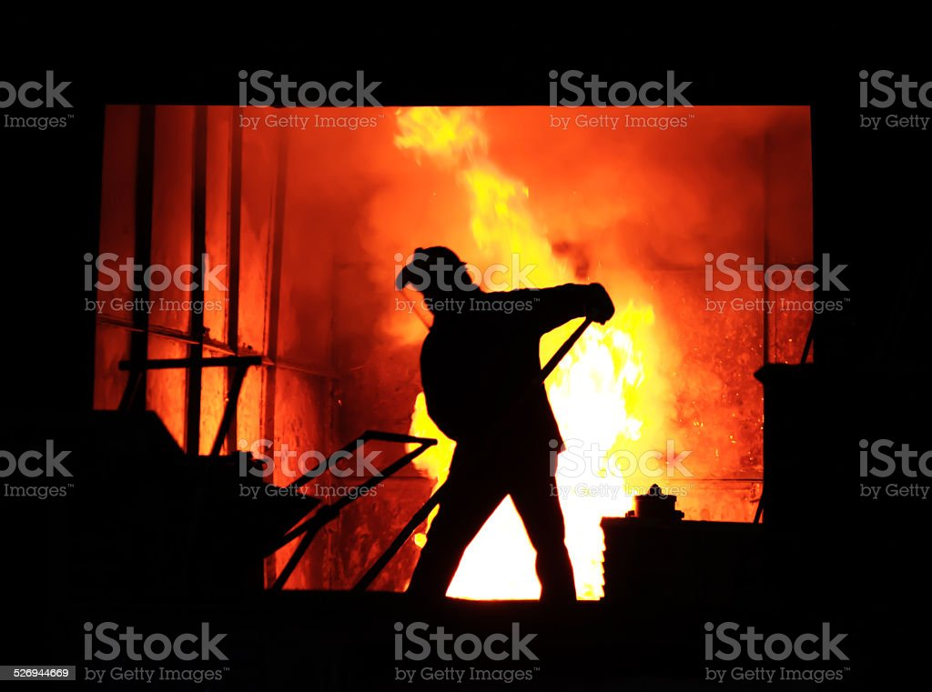 Man working in the splashing molten iron - Stock Image stock photo