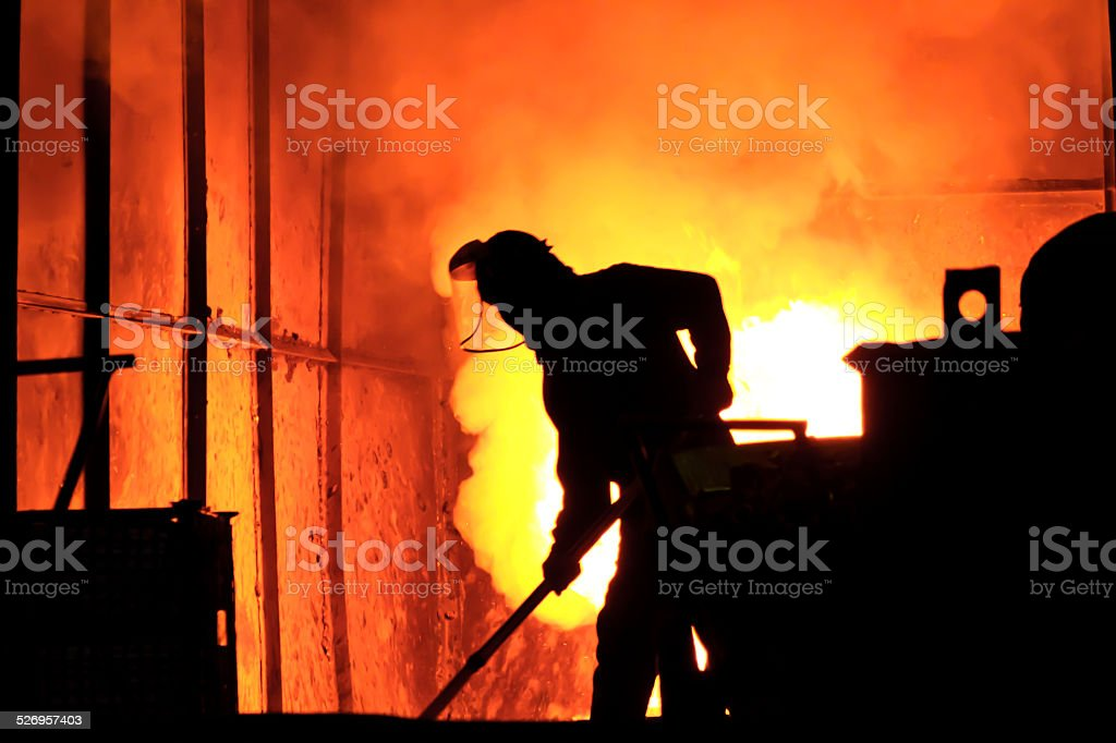 Man working in the splashing molten iron - Stock Image stock photo