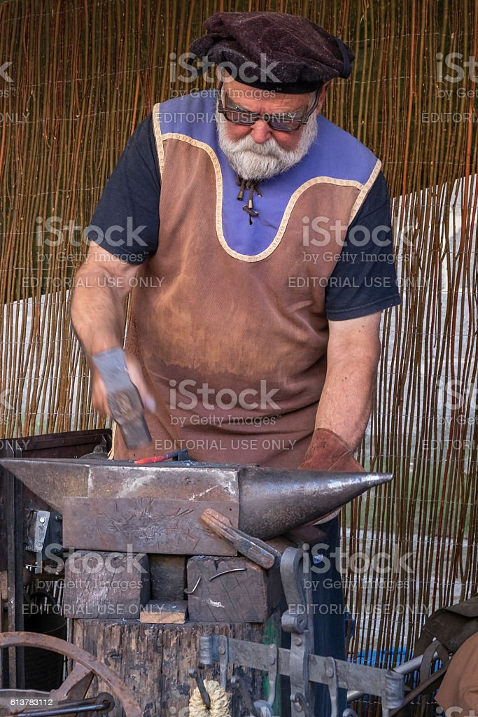 Man working iron in a medieval market in Ávila stock photo