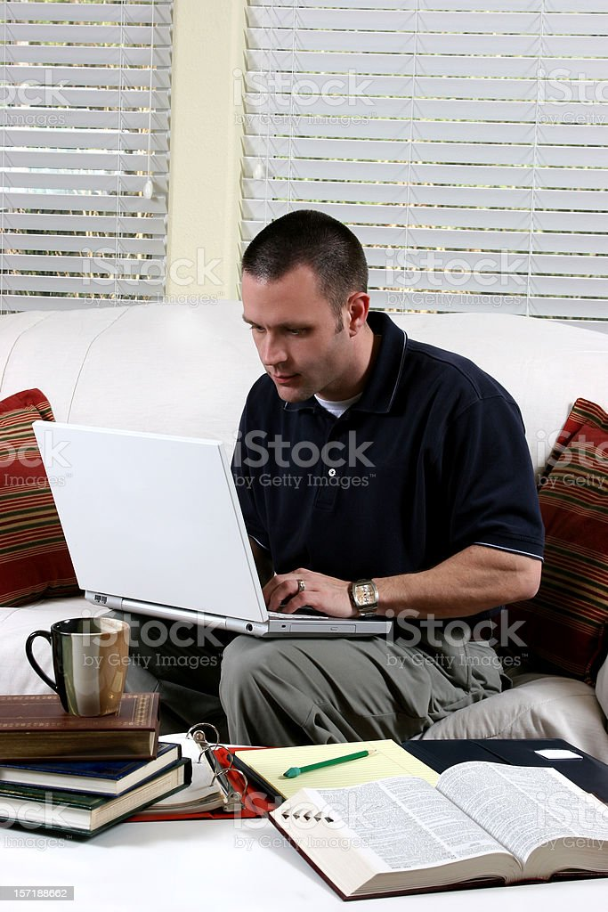 Man working. Laptop computer at home.  Books on coffee table. royalty-free stock photo