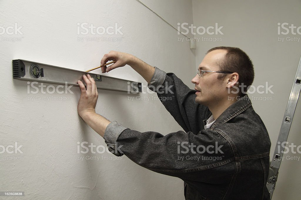 Man working level. Master measures the wall. royalty-free stock photo