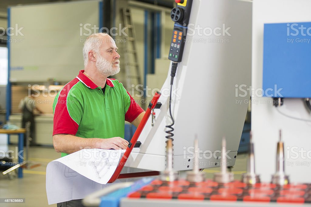 Man Working On A CNC Machine stock photo