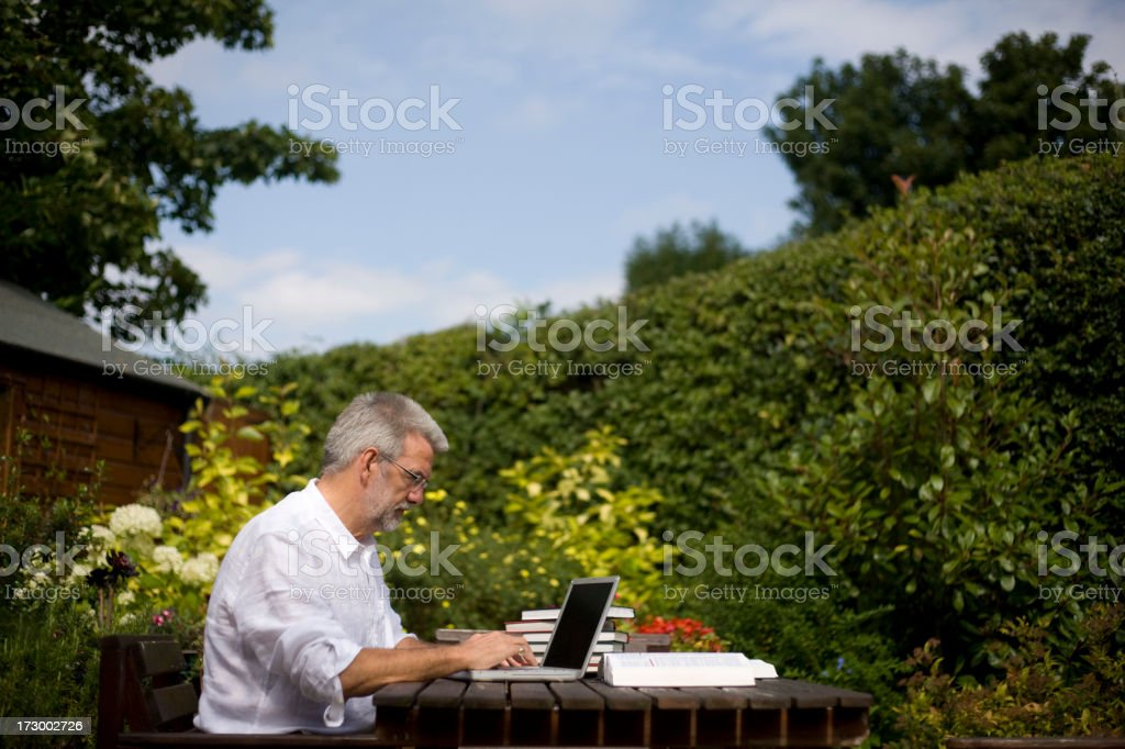 A man working on a laptop in the backyard royalty-free stock photo