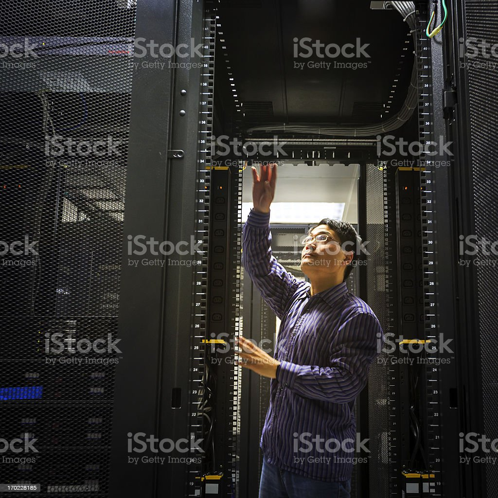 A man working on a server overhead royalty-free stock photo