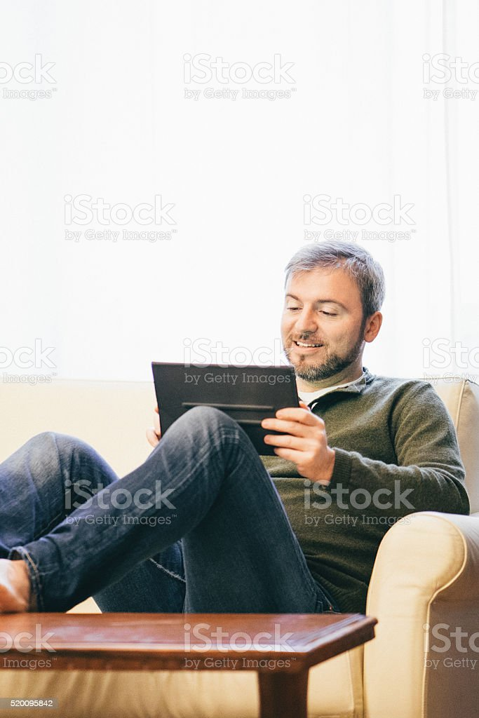 Man Working On A Tablet At Home stock photo