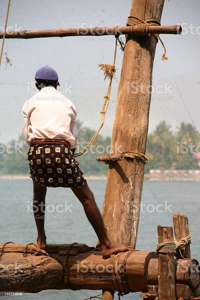 Man working on a wooden fishing platform royalty-free stock photo