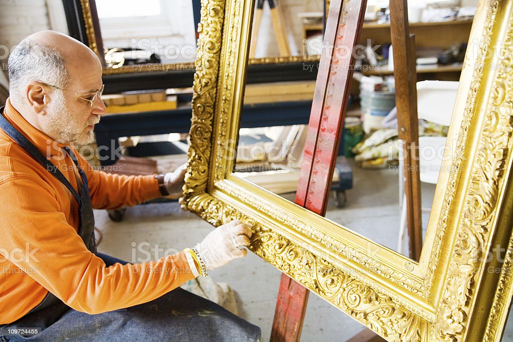 Man Working on Antique Gold Picture Frame stock photo