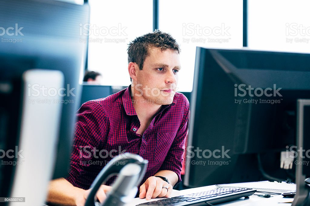 Man working on computer in modern office stock photo