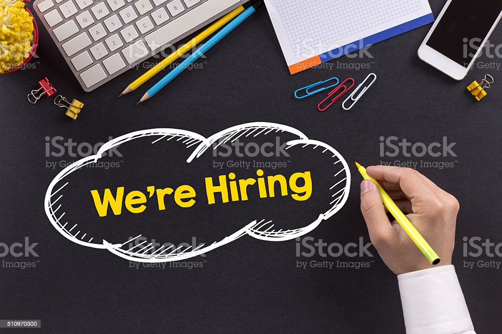 Man working on desk and writing We're Hiring stock photo