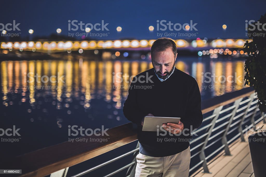 Man working on digital tablet at night stock photo