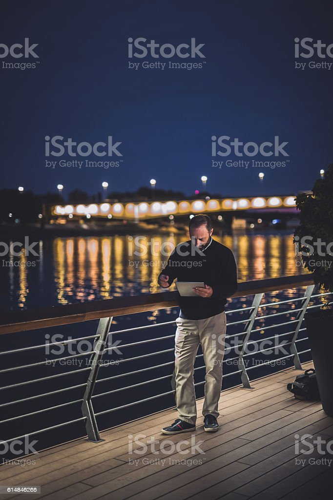 Man working on digital tablet outdoors stock photo