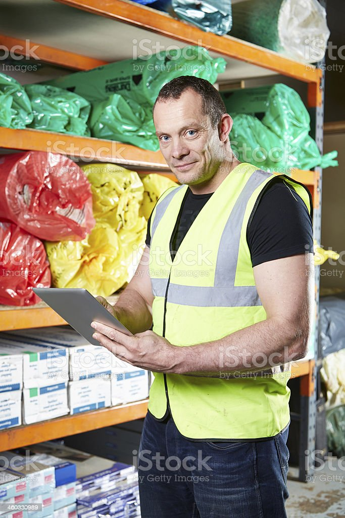 Man working on electronic tablet in warehouse stock photo