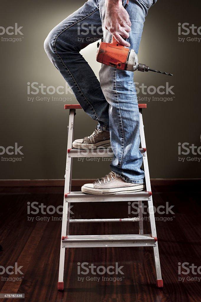 Man working on ladder stock photo