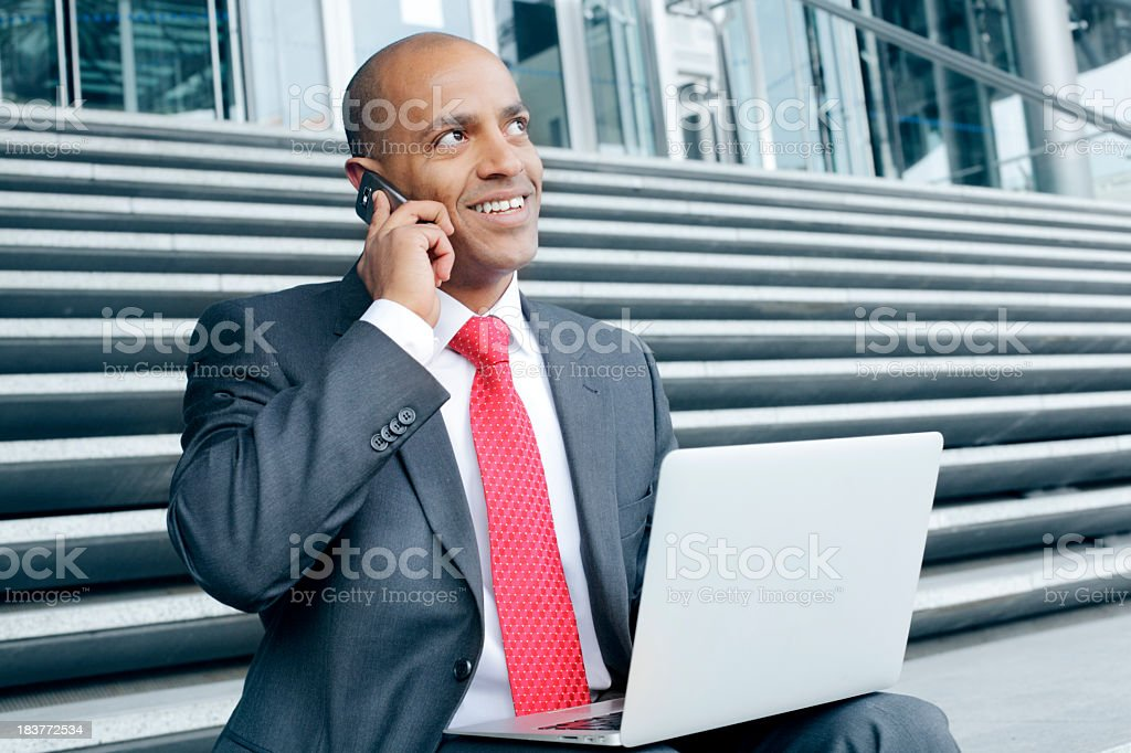 Man working on laptop and phoning royalty-free stock photo