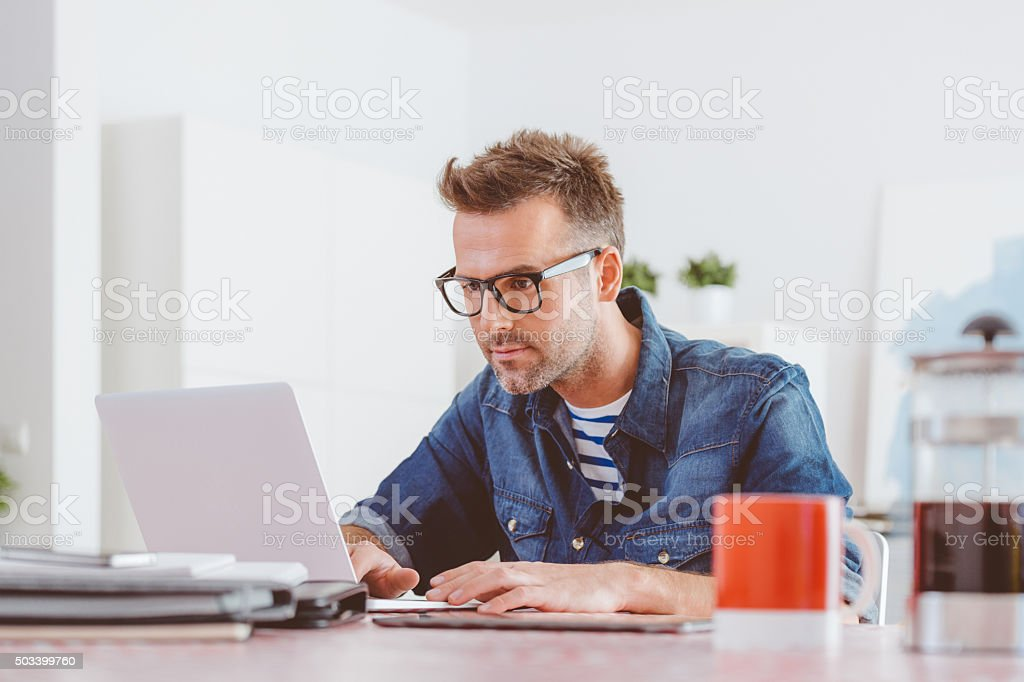 Man working on laptop at home stock photo