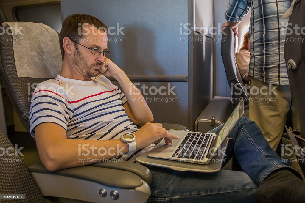 Man working on laptop in aircraft cabin during his travel stock photo
