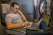 Man working on laptop in aircraft cabin during his travel
