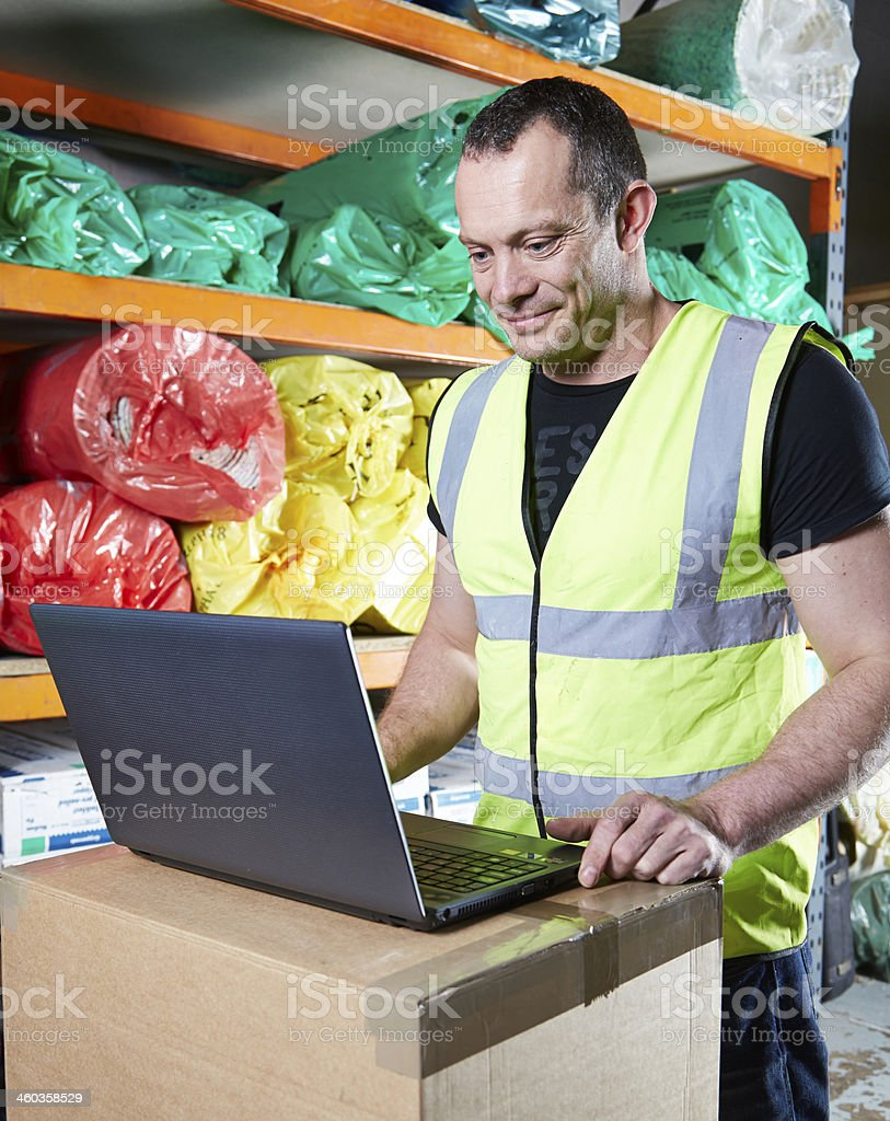 Man working on laptop in warehouse stock photo